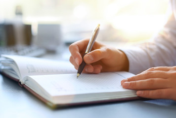 Businesswoman makes a note in notebook.