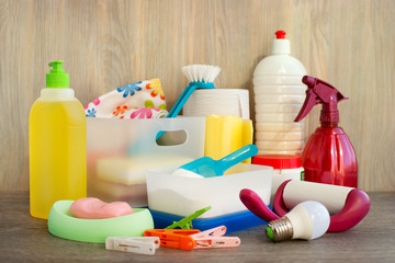 Household items are collected in a heap. Many household items in the form of washing powder, washing liquid, brushes, sponges, soap, LED lamp, clothespins, a roll of napkins.