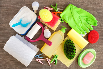 Household items on a wooden background. Washing powder, rubber gloves, soap, a roll of paper, sponges are household items for the cleanliness of the house.