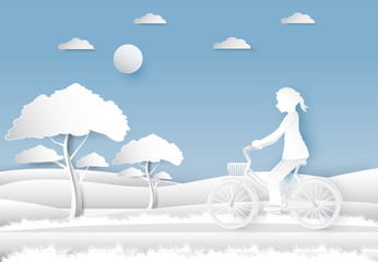 Girl riding a bicycle in the field on blue sky paper art, paper cut style