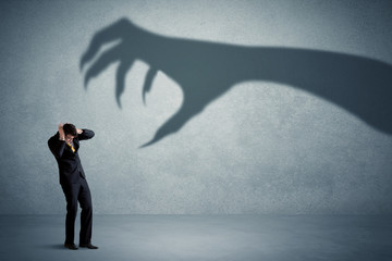 Business person afraid of a big monster claw shadow concept on background Wall mural