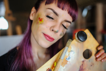 portrait of beautiful female artist with purple hair and dirty hands