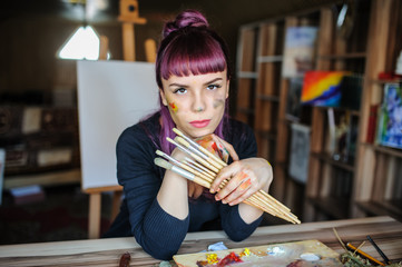 female artist with purple hair and dirty hands