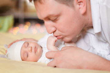 Young happy father holding and kissing newborn baby. Concept of newborns and parents.