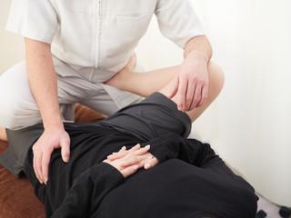 股関節・腰回りの筋肉を伸ばすストレッチを受ける女性