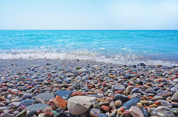 Seascape and coastal pebbles in sunny day. Marine panoramic view.