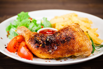Roasted chicken leg with french fries on wooden background