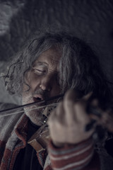 Retro toned image of  man with gray hair and beard singing as he plays a violin