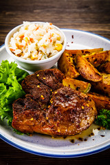 Grilled steak with baked potatoes and vegetables served on wooden table