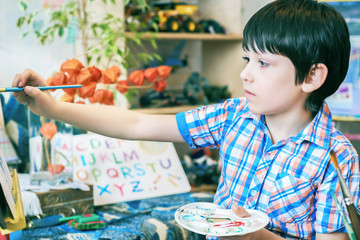 Young boy sitting in front of easel painting a fish, holding a brush in hand. Boy is getting ready to become an artist.