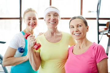 Happy mature women with toothy smiles looking at you during training in sports center