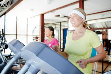 Happy aged woman running on treadmill in sports center with her friend on background