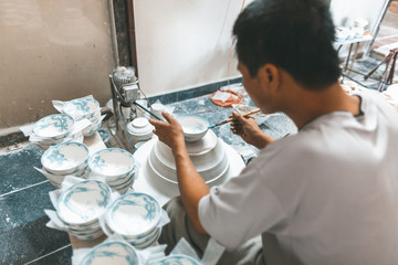 Man painting on ceramics bowls in Vietnam