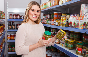 Positive woman customer holding pickle goods in  food shop