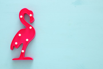a plastic flamingo lamp with leds over blue wooden background. holiday summer concept.