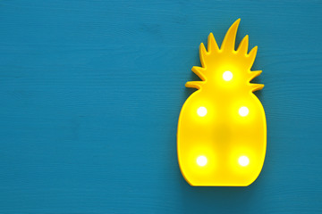 a plastic pineapple lamp with leds over blue wooden background. holiday summer concept.
