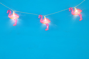 a plastic flamingo garland lights over blue wooden background. holiday summer concept.