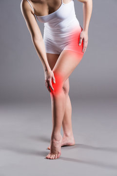 Woman with pain in thigh and knee on gray background