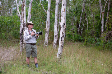 Photographer Holding Camera And Long Lens In Bushland