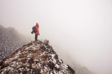 Young traveller woman wearing backpack, red jacket and hat standing in fog mountain trekking above clouds and valley. No way, lost in mountains