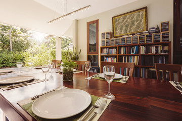 Luxury Tropical dining room with bookshelf, dvd collection, open outdoor space. Plates and vine glasses on wooden table, beautiful summer villa design