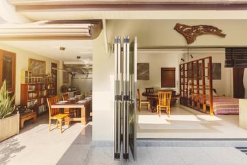 Big open dining room with bookshelf and bedroom with folding doors in luxury villa hotel resort. Summer, tropical wether, sun light, outdoor space