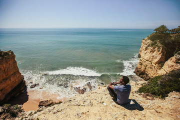 African man seating  on beautiful cliff, looking to ocean, enjoy travel holiday. Algarve, Portugal