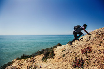 Man climbing and walking on ocean cliff. Beautiful sea landscape, sunny day