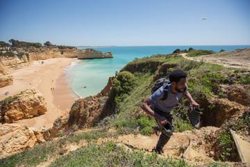 African man traveler walking on beautiful cliff ocean beach