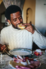 Portrait of african man seating in dining room at home, having breakfast .
