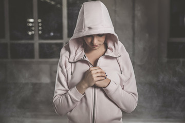 Waist up portrait of mysterious girl in pink hood standing in white vapour. Hands are peacefully folded up on chest. Eyes are directed on floor