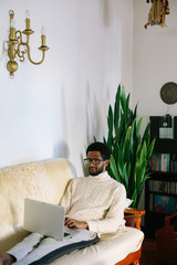 Portrait of young freelancer african man wearing glasses seating on sofa using laptop at home