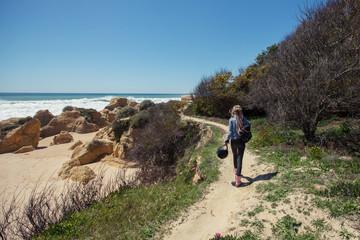 Woman holding helmet for motorcycle travel walking on ocean beach. Algarve, Portugal