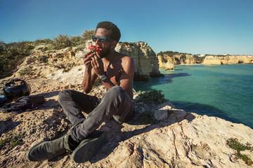 African man in motorcycle travel taking brake, eating tomato on sunny ocean beach