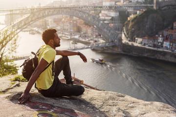 Traveler man enjoying city view in Porto, famous iron bridge and Douro rive on background