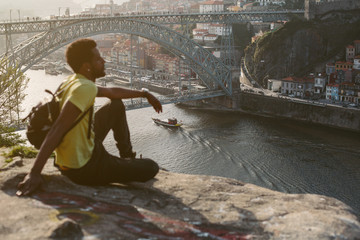 Traveler african man enjoying city view in Porto, famous iron bridge, boat and Douro rive on background