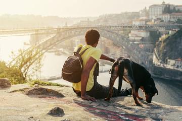 Traveler man with dog enjoying city view in Porto, famous iron bridge and Douro rive on background