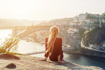 Traveler female enjoying city view in Porto, famous iron bridge and Douro rive on background, dreadlocks hairstyle