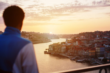 Young african traveler man meets sunset standing on the view point in front of Douro river and Dom Luis I bridge in Porto, Portugal
