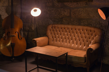 Modern jazz bar interior design, leather sofa, cello music instrument, lamps. Stone wall on background, brutal atmosphere