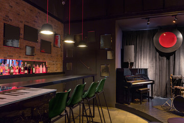 Modern jazz bar interior design, stage with black piano, lamps above bar counter