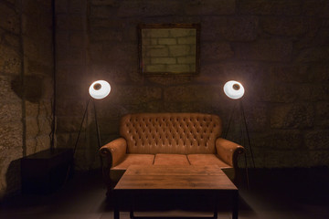 leather sofa, lamps and table in dark interior. Stone wall on background, brutal atmosphere