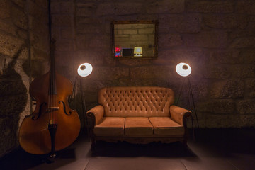 leather sofa, cello music instrument, lamps in dark interior. Stone wall on background, brutal atmosphere