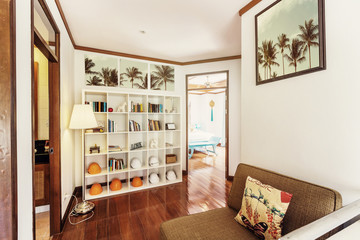 Small living room interior. Shelfs with books and construction helmets like decor elements, tropical palm trees in pictures on the wall, open doors to bedrooms