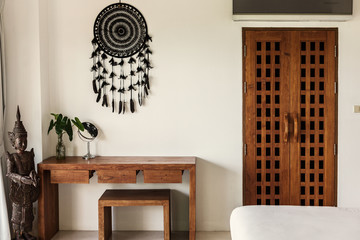 Simple luxury villa bedroom interior. White colours, wooden door and table, Buddha statue and Dreamcatcher on the wall