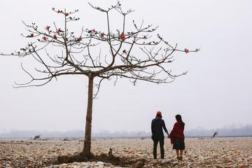 Travel couple standing under tree in fog river beach, fresh morning time. Chitwan national park, Nepal