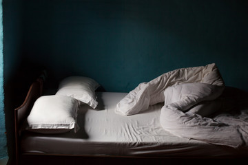 Bed with white blanket, blue walls in village house