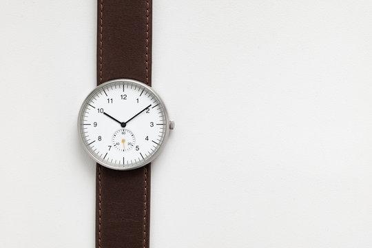 Minimalist wristwatch white dial on white background