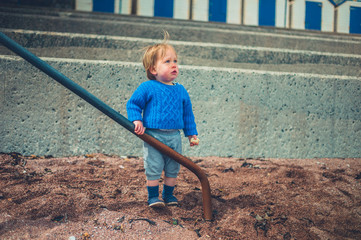 Little boy by railing outdoors