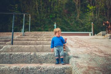 Little toddler eating banana on steps outside
